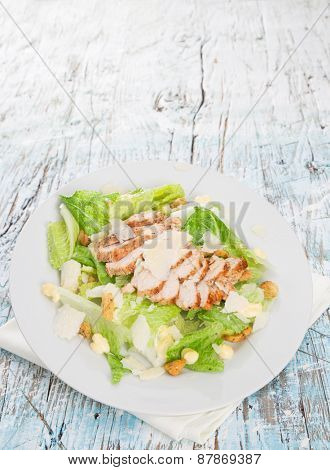 Caesar salad with chicken and greens on wooden table
