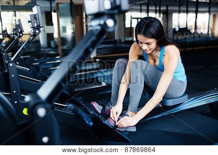 Young woman preparing to exercise on a simulator at gym