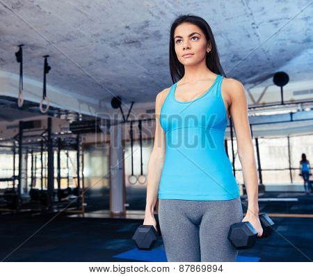 Young fit woman holding dumbbells at gym and looking away
