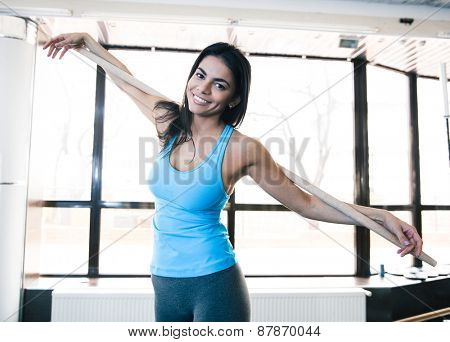 Smiling young woman holding stick at fitness gym
