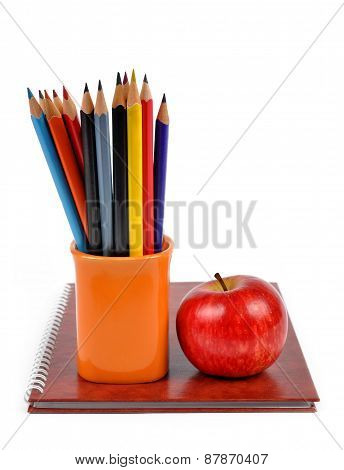 Workbook and color pencils with apple
