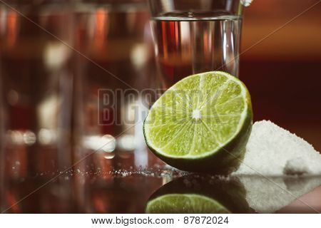 Two Shots Of Tequila With Lime And Salt On A Wooden Table Bar On The Background Of Bright Lights Of
