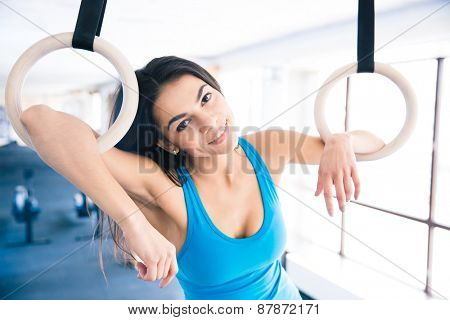 Happy woman with gimnastic ring at gym looking at camera