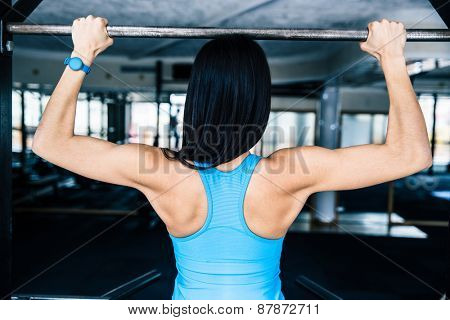 Back view portrait of a woman working out at gym