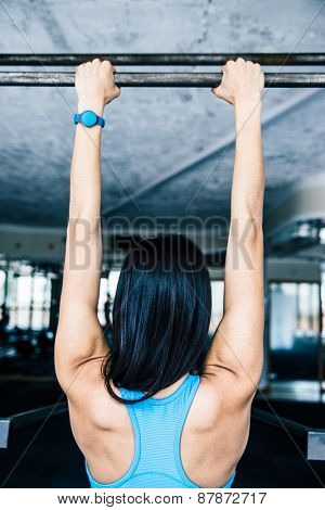 Back view portrait of a sports woman working out at gym