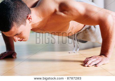 Man exercising  in gym - push ups