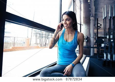 Smiling fit woman talking on the phone at gym and looking at window