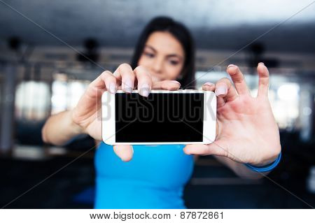 Woman making selfie photo on smartphone at gym