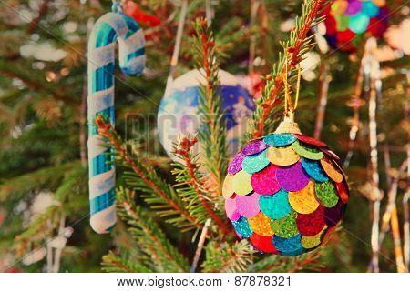 Multicolored Christmas Ball On A Pine Branch Taken Closeup.