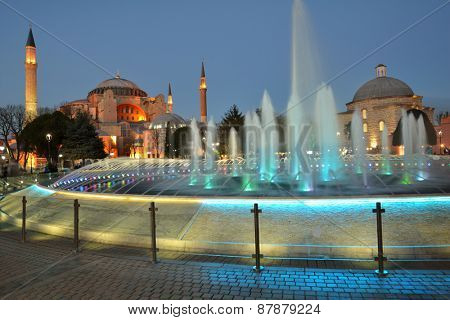 ISTANBUL, TURKEY - MARCH 21, 2014: People resting near the fountain against the Hagia Sophia. Hagia Sophia is one of the greatest surviving examples of Byzantine architecture