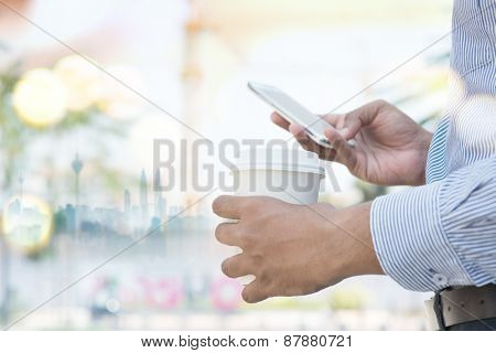 Man hand holding take away coffee cup while using smartphone, outdoors business concept.