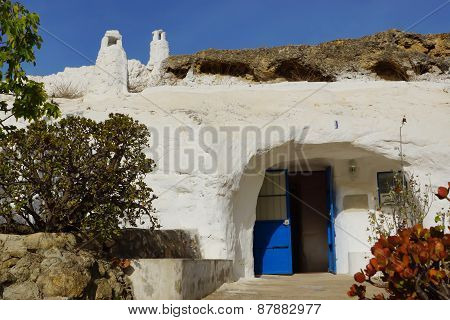 Troglodytes cave in Spain, the white house with a chimney, a blue door, plants
