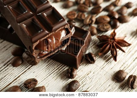 Stuffed chocolate with coffee beans on wooden table, closeup