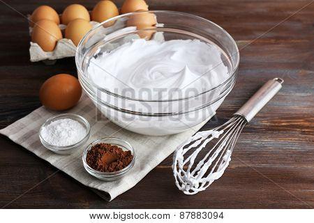 Whipped egg whites for cream on wooden background