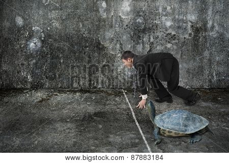 Businessman And Turtle Are Ready To Race On Concrete Floor