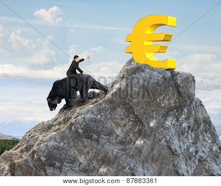 Businessman Riding Bear Pursuing Gold Euro Symbol On Mountain Peak