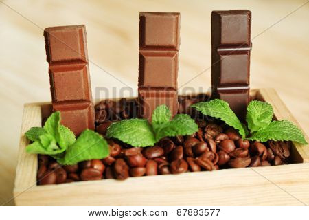 Still life with set of chocolate in wooden box of coffee grains, closeup