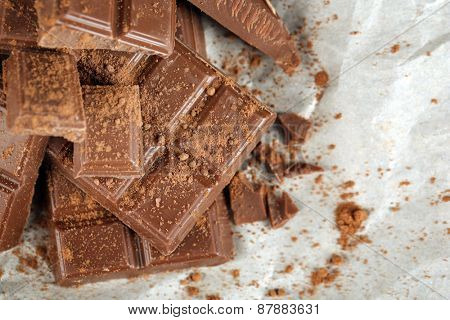 Pieces of chocolate with cocoa on parchment, closeup