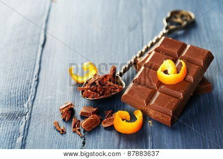 Pieces of chocolate with orange peels on color wooden background
