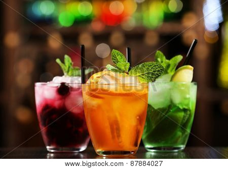 Glasses of cocktails on bar background