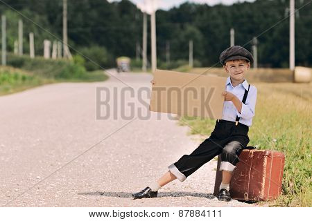 Boy Hitch Hiking On The Road