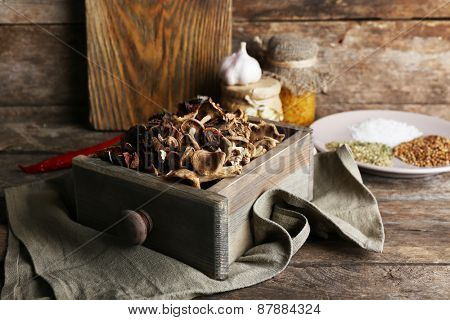 Dried mushrooms in crate on wooden background