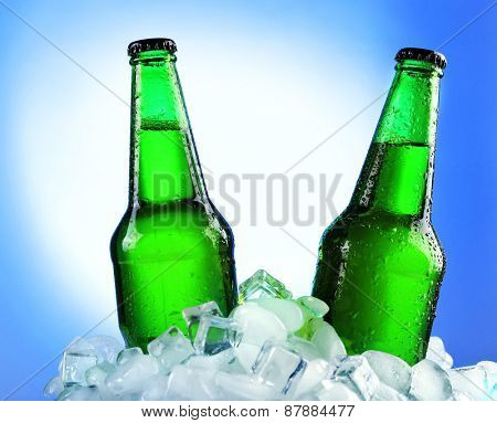 Glass bottles of beer in ice cubes on color background