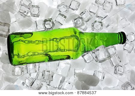 Glass bottle of beer on ice cubes background