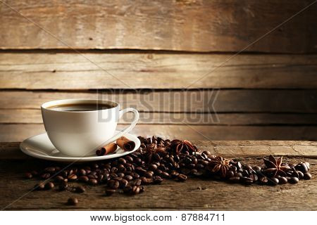 Cup of coffee with grains and spices on wooden background
