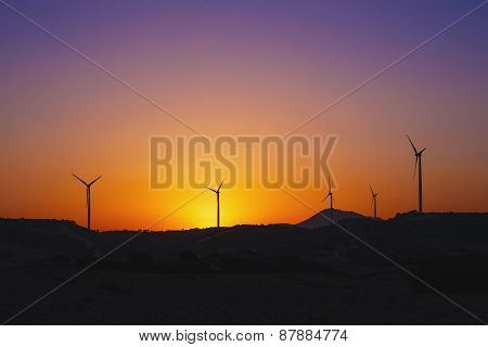 Wind turbine power generator at sunset