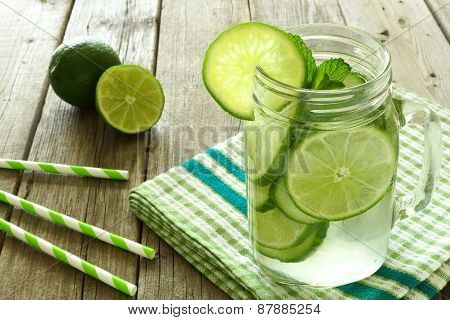 Detox water with lime and cucumbers in jar against wood