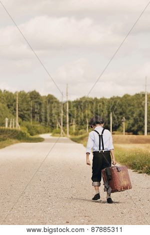 Young Boy Walking Away With Suitcase