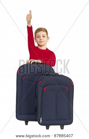 Smiling boy showing thumbs up with travel bags