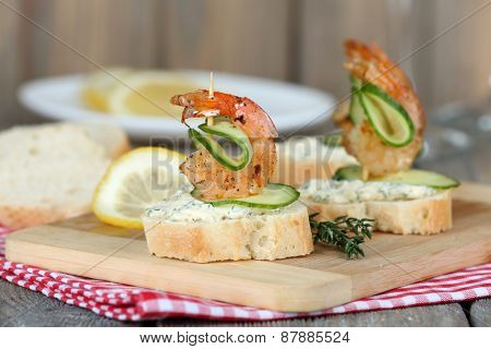 Appetizer canape with shrimp and cucumber on table close up