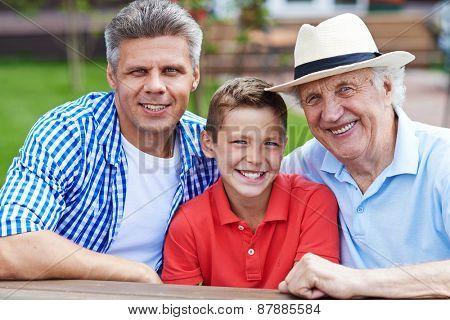 Happy senior man, young man and boy looking at camera