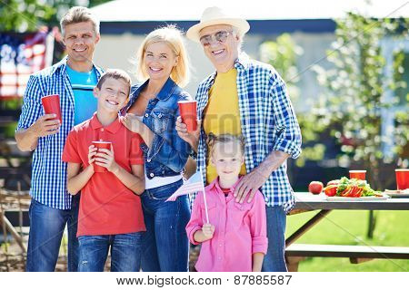 Happy senior man and young couple with two kids spending weekend outdoors