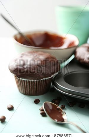 Tasty homemade chocolate muffins and cup of coffee on wooden table, on light background