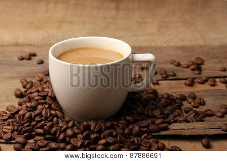 Cup of coffee with grains on rustic wooden table background