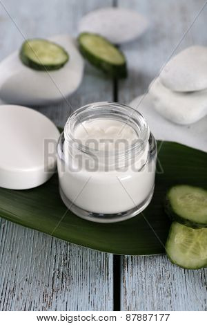 Cosmetic cream with slices of cucumber and spa stones on wooden background