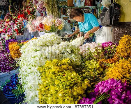 Woman creates floral arrangements for sale at an outdoor market in Bangkok