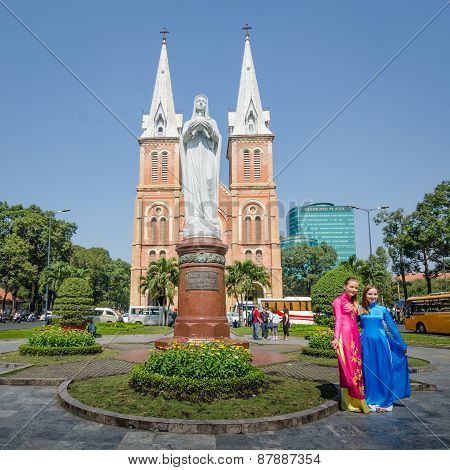 Two Women pose in front of Saigon's Notre-Dame Basilica