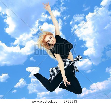 Jumping woman on sky background