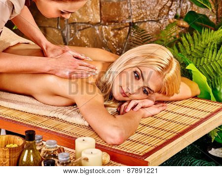 Beautiful young woman getting massage in spa.