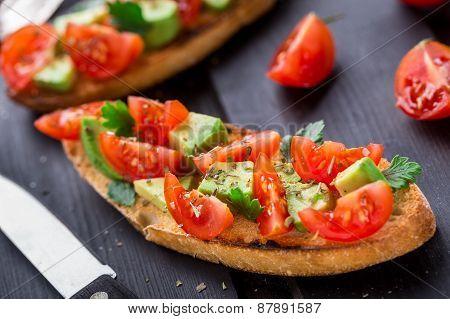 Bruschetta with tomato, avocado and herbs