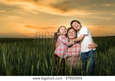 happy mother and childs in green field at sunset