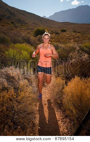 Blonde Female Trail Runner Running Through A Mountain Landscape