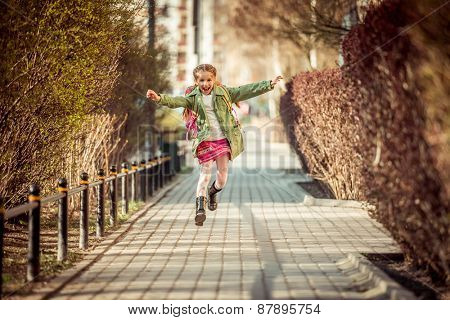 happy little girl running home from school