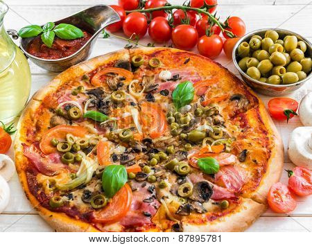 Pizza with ham and olives on a wooden background surrounded by food ingredients