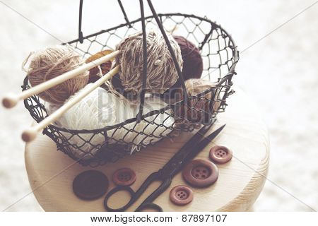Vintage knitting needles, scissors and yarn inside old wire basket on wooden stool, still life photo with soft focus
