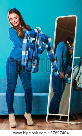 Fashionable Woman Trying Plaid Shirt In Front Of Mirror